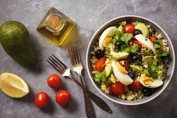 Bulgur salad with eggs, avocado, tomatoes and olives.