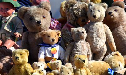 Braune und gelbe, große und kleine Teddys auf einem Flohmarkt