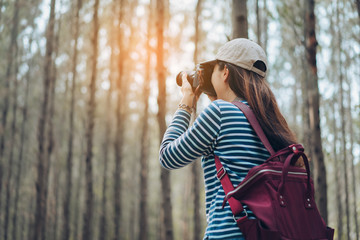 Woman photographer taking photo in the forest with backpack and travel lifestyle relaxation enjoy on autumn and summer weekend.