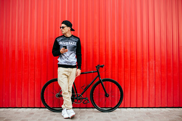 Young hipster man with smartphone, standing near the bike