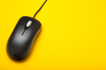 Computer mouse with blank space for text on a yellow background.