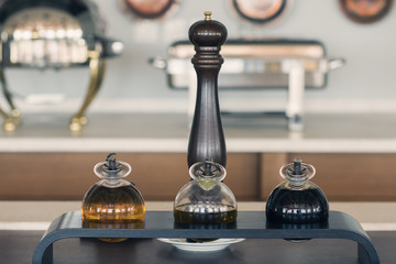 Round bottles with olive oil and basil sauce on the retro kitchen