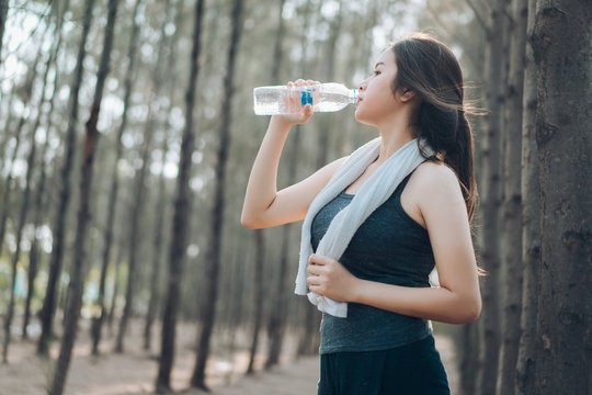 Beautiful asian woman drinking water bottle in the forest nature for relaxing recovery active healthy lifestyle.