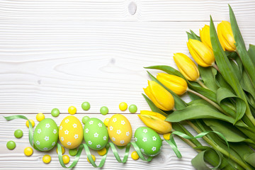 Easter eggs and tulips on wooden background.