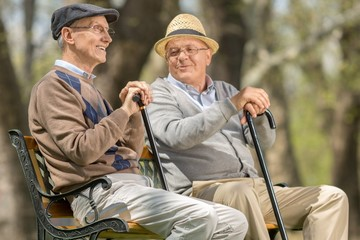 Two elderly men seated on a bench outdoors