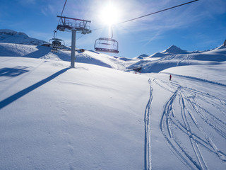Ski lift with seats going over the mountain and paths from skies and snowboards. France, Meribel, 2018