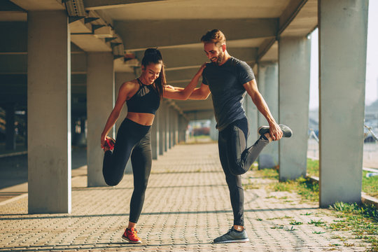 Young couple warming up in urban environment before jogging