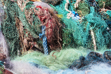 Pile of old and used fishing nets colored, floating and blue rope on the quay, in very bad condition, waste from the sea. Gargano Coast, National park on Puglia on Italy