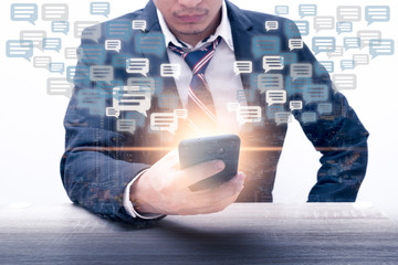 The double exposure image of the businessman using a smartphone overlay with cityscape image and message box icon. The concept of communication, business, social media and internet of things.
