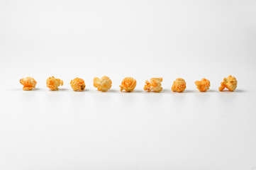 Delicious popcorn in a line on the white background