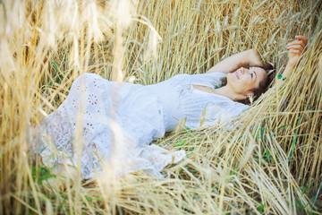 beautiful woman in a white dress lies in the ears of corn
