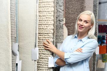 Sklep z dywanami. Sprzedawca doradza pokazując wzory na ekspozycji.