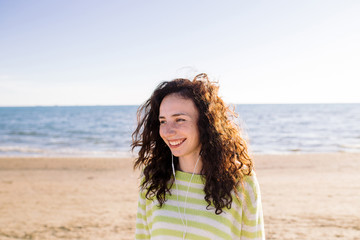 Laughing young woman have fun and listening to music on beach on background of sea. Curly girl with earphones and phone outdoor