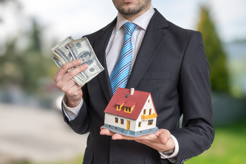 Real estate agent is holding small house and money in hands.