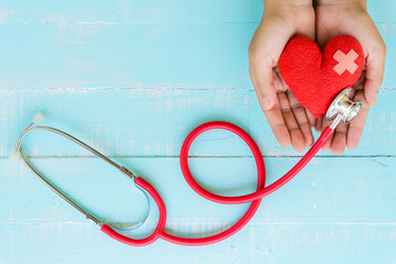 Healthcare and medical concept. Woman hand holding red heart with Stethoscope, notepad or notebook, thermometer and yellow Pill on Pastel white and blue wooden table background texture.