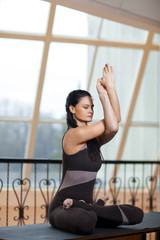 Young attractive yogi woman in a dark jumpsuit practicing yoga concept, sitting in variation of Gomukasana exercise, Cow Face pose, wearing sportswear, large window background