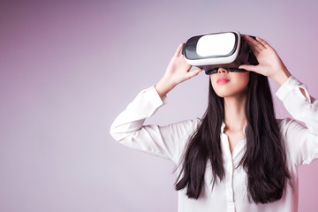481bbcb254 Studio Portrait of young beautiful smiling Asian woman in white shirt  watching video in virtual reality