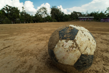 close up old football on ground at a dirt pitch