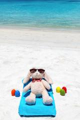 Osterhase im Urlaub am Strand mit bunten Ostereiern