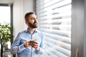 A man by the window holding a cup of coffee. Smart home.