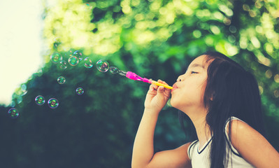 Asian cute girl playling BLowing Bubbles Together at the Field