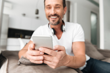 Satisfied mature man holding mobile phone