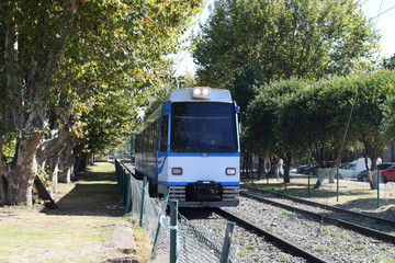 the tram (train) is traveling by rail from the platform