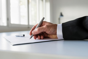 Low view of businessman hand signing business contract
