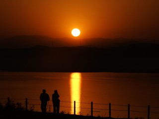 オレンジ色の太陽とカメラマンのシルエット