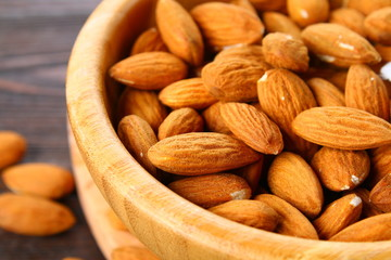 Raw dry nuts of almonds in a wooden bowl on a wooden table.