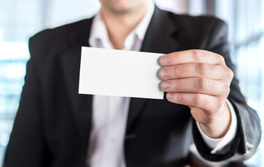 Business man holding empty white business card in modern office building. Free blank copy space.