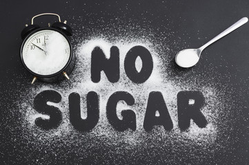 """Spoonful of sugar and an alarm clock, covered with sugar on a dark table, sugar written the text """"no sugar."""""""