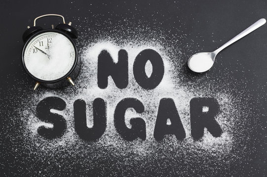 "Spoonful of sugar and an alarm clock, covered with sugar on a dark table, sugar written the text ""no sugar."""