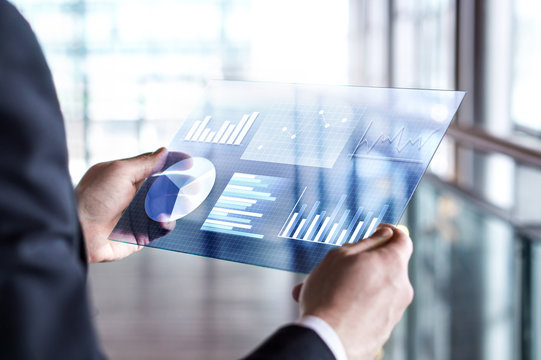 Transparent futuristic tablet. Business man using virtual touch screen. Modern mobile technology in accounting, finance, data and analytics. Internet of things (IOT) and augmented reality concept.