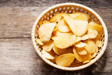 Crispy potato chips in a wicker dish