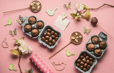 Easter concept, various decorations, chocolate eggs in a box, gift wrapping paper, lined on a pink background, top view flat lay