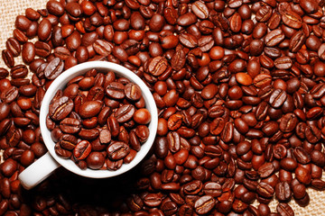 White cup and coffee beans on the background of sacking. view from above