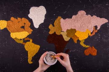 Hands with a jar of spices against the background of the world map which is laid out from multi-colored seasonings