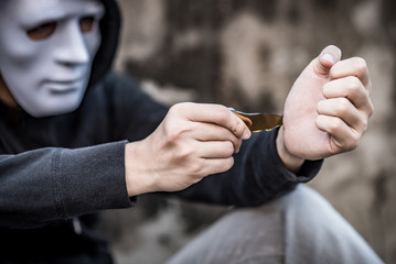 Mystery man in white mask wearing hoody jacket try to cut his wrist with the debris of broken bottle. depression self destruction suicidal addiction. major depressive disorder concept