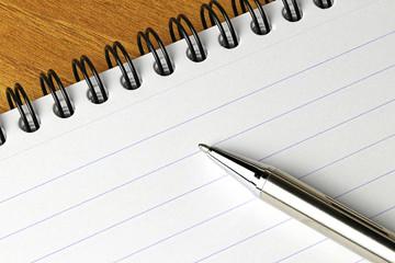 Paper notepad and pen closeup