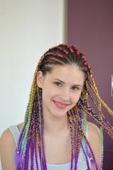Девушка с модным набором разноцветных косичек Канекалон. Цветные искусственные пряди волос. Материал для плетения.