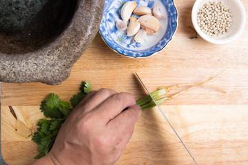 Chef cutting coriander on wooden board