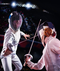 Fencing sport for women fencer. Fia female athlete in fight epee competition. Large group fans on tribunes with lens flare illumination.