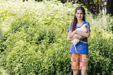 Portrait of smiling girl holding chicken while standing against plants at yard