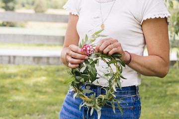 Woman making a wreath out of grass and flowers