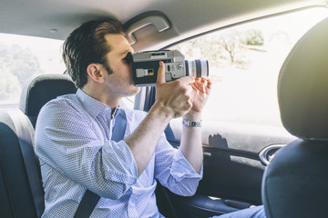 Man using video camera while sitting in car on sunny day