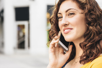 Smiling beautiful woman looking away while talking on smart phone in city