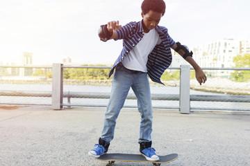 Confident boy skateboarding on bridge in city park