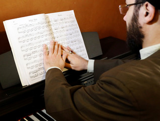 Shi'ite Muslim scholar Sayed Hussein al-Husseini, 38, looks at musical notes at his home in Dahieh