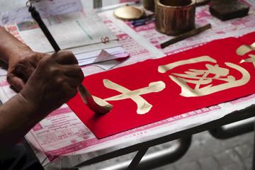 Un calligraphe chinois qui peint sur un banderole